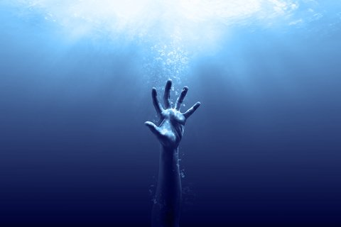 hand reaching up while drowning