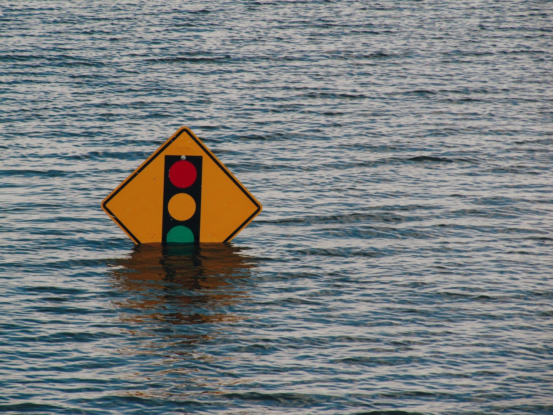 Traffic light sign halfway underwater from flood waters.